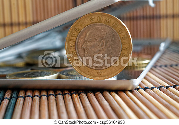 Pile of Turkish coins with a denomination of one lira in mirror reflect wallet lies on wooden bamboo table background - back side - csp56164938