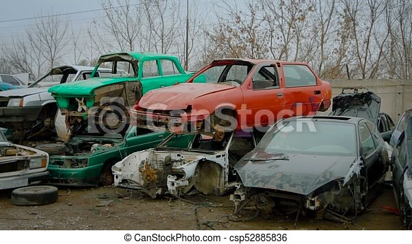 Piles of old broken rusty cars on wrecking yard