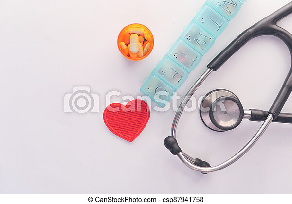 pill box and container stethoscope on white background - csp87941758