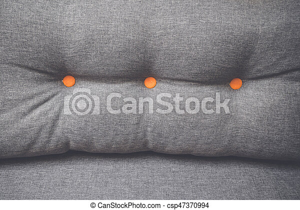 Pillow in grey color with orange buttons - csp47370994