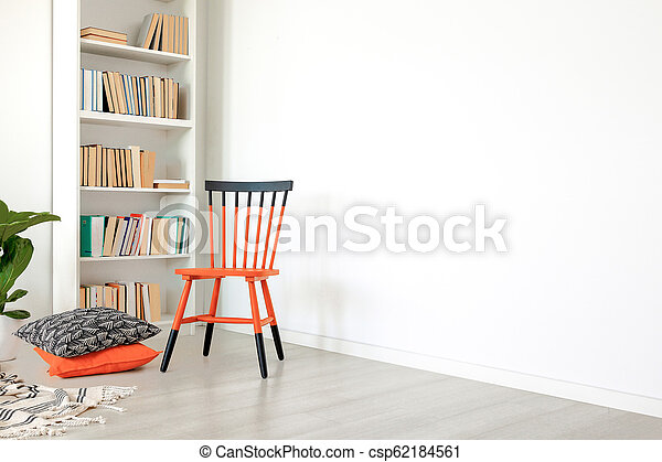 Pillows next to orange and black chair in white room interior with copy space on empty wall. Real photo - csp62184561