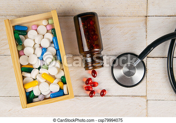 Pills in botle and wooden box with stethoscope and heart on white wooden table. Medical concept. Top views with clear space - csp79994075