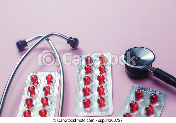 Pills, stethoscope and medical masks on pink background - csp84363727
