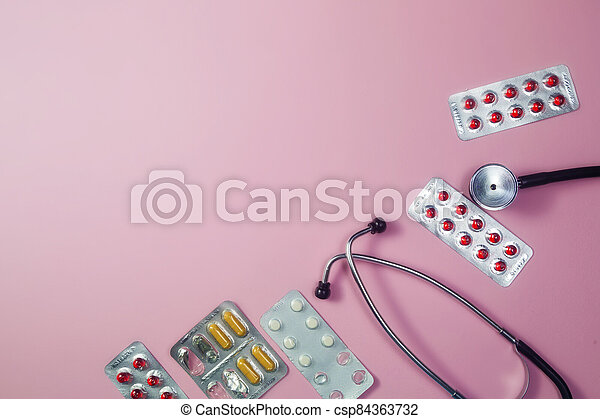 Pills, stethoscope and medical masks on pink background - csp84363732