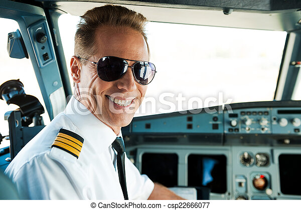 Pilot in cockpit. Rear view of confident male pilot looking over shoulder and smiling while sitting in cockpit  - csp22666077