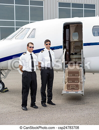 Pilots Standing By Private Jet - csp24783708