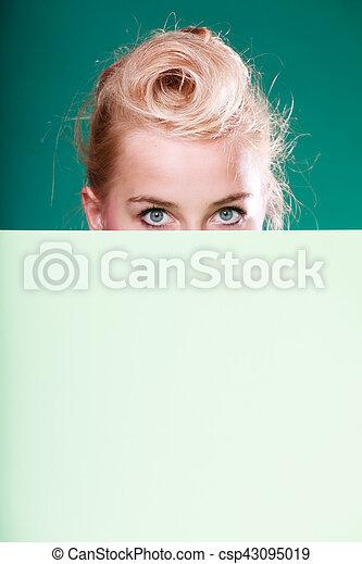 Pin up woman eyes behind white sign - csp43095019