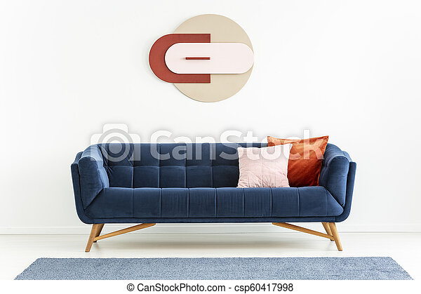 Pink and orange pillows on blue sofa in white apartment interior with  poster and carpet. Real photo