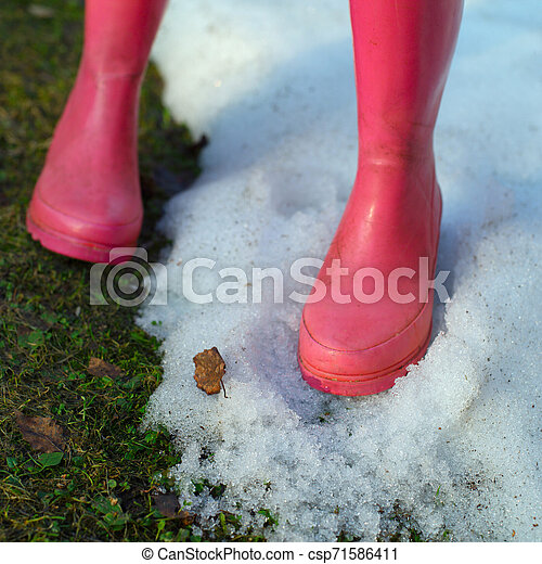 Pink boots on the snow and grass - csp71586411