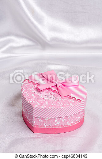 Pink heart shaped gift box with bow over white satin - csp46804143