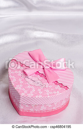 Pink heart shaped gift box with bow over white satin - csp46804195