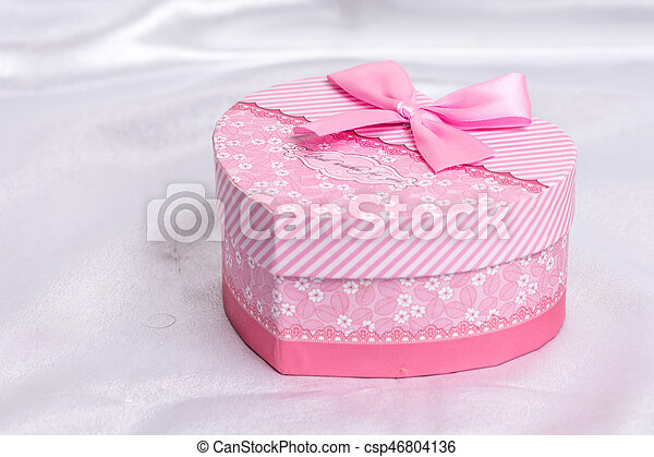 Pink heart shaped gift box with bow over white satin - csp46804136