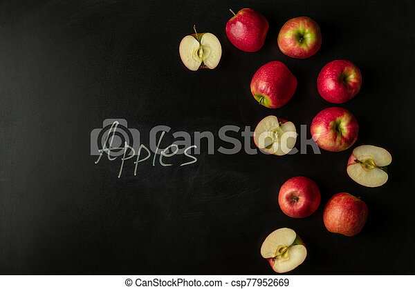 Pink lady apples on black background with text - csp77952669