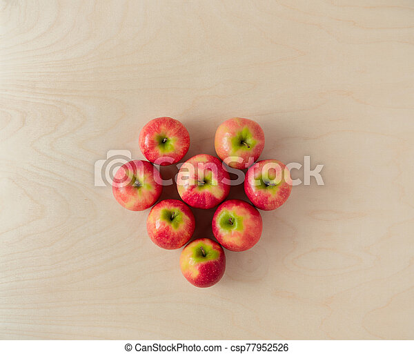 Pink lady apples on wooden background. Heart shaped layout - csp77952526
