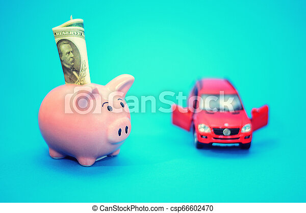 Pink piggy bank with a car on the table. Tinted. Concept of saving finances and contributions to property. - csp66602470