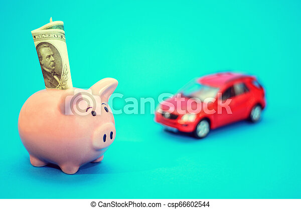 Pink piggy bank with a car on the table. Tinted. Concept of saving finances and contributions to property. - csp66602544