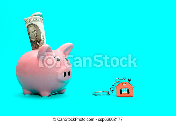 Pink piggy bank with a house on the table. Tinted. Concept of saving finances and real estate deposits. - csp66602177