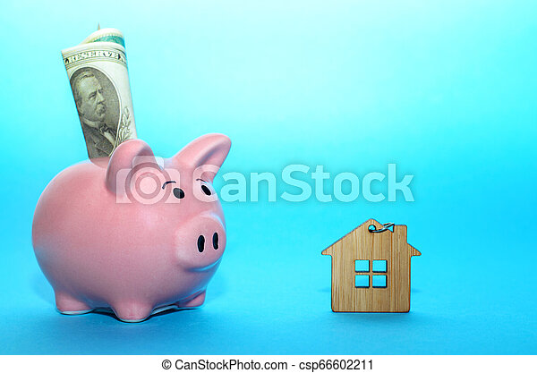 Pink piggy bank with a house on the table. Tinted. Concept of saving finances and real estate deposits. - csp66602211