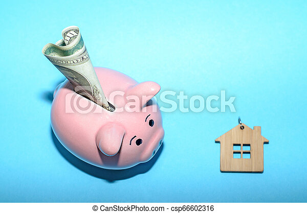 Pink piggy bank with a house on the table. Tinted. Concept of saving finances and real estate deposits. - csp66602316