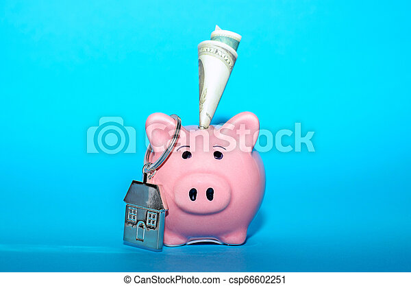 Pink piggy bank with a house on the table. Tinted. Concept of saving finances and real estate deposits. - csp66602251