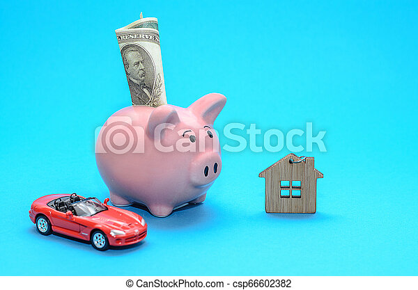 Pink piggy piggy bank with a house and a car on the table. Tinted. Concept of saving finances and real estate deposits. - csp66602382