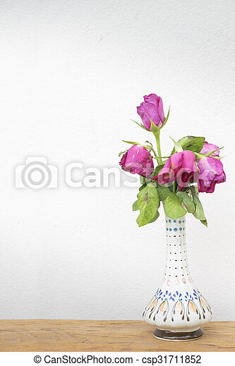 Pink rose flowers in vase on wooden table over wall grunge background - csp31711852