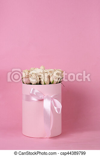 Bunch of delicate pastel colored roses in pink gift box with satin bow on pink background.