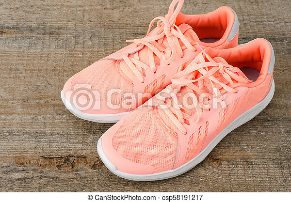 Pink sneakers on wooden background - csp58191217