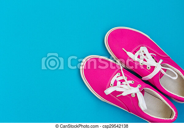 Pink sneakers with white laces on a blue - csp29542138