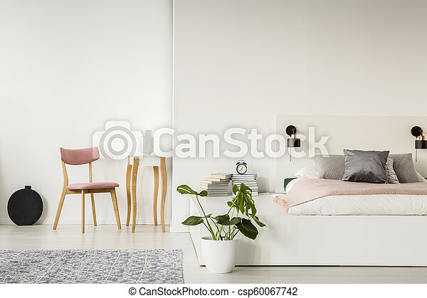 Pink wooden chair in white bedroom interior with plant next to bed on  platform. Real photo