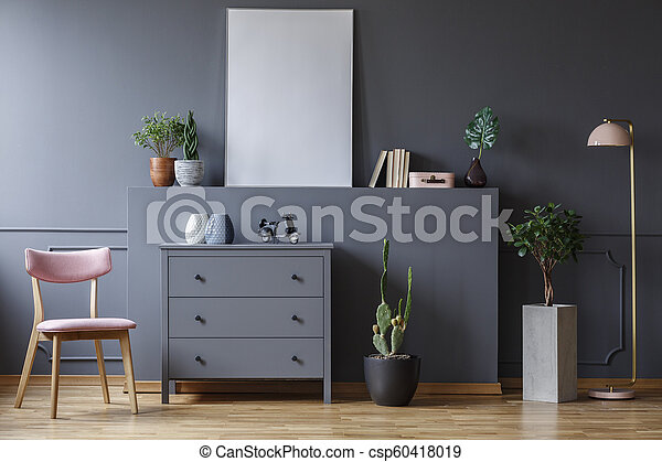 Pink wooden chair next to grey cabinet in living room interior with plants and poster. Real photo - csp60418019