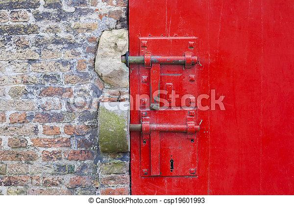 Puerta roja pintada con cerraduras y ladrillos - csp19601993