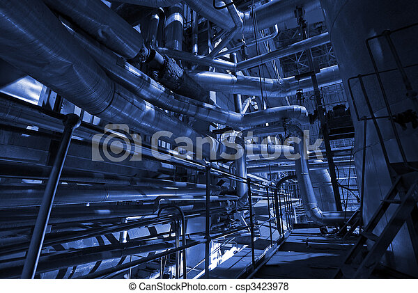 Pipes, tubes, machinery and steam turbine at a power plant in blue tone - csp3423978