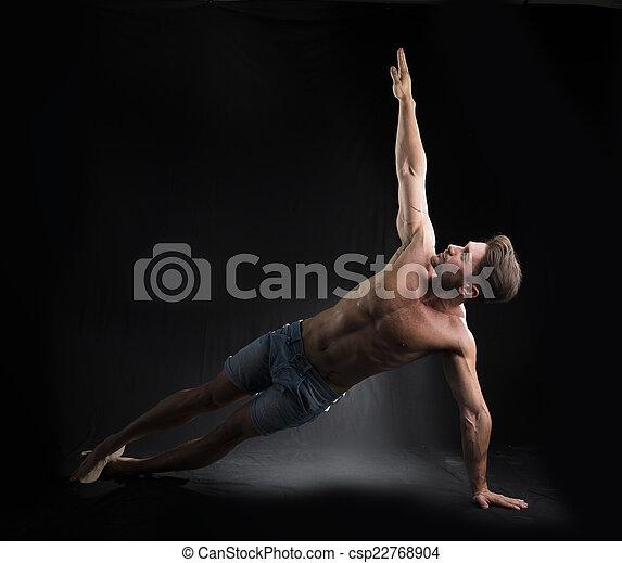 Joven hombre sexy sin camisa estirandose en el suelo - csp22768904