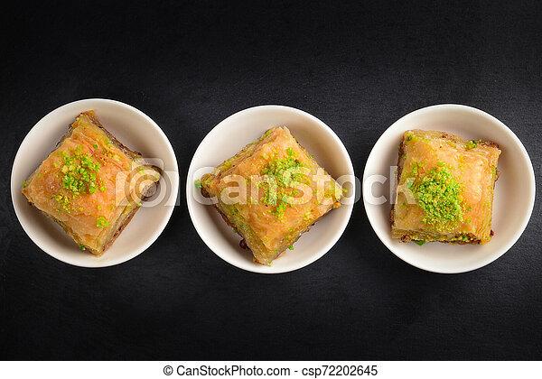 Pistachio baklava on a black plate. Dessert. - csp72202645