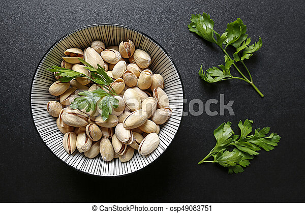 pistachio nuts in a bowl on black background - csp49083751