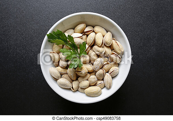 pistachio nuts in a bowl on black background - csp49083758