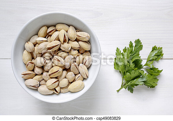 pistachio nuts in a bowl on white wooden background - csp49083829