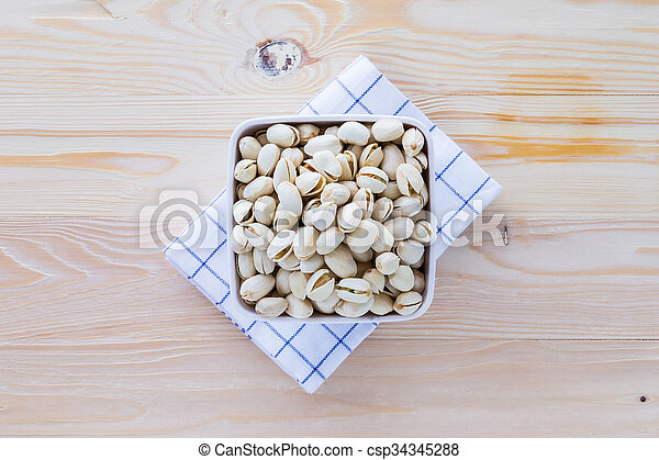 Pistachio nuts in a bowl - csp34345288