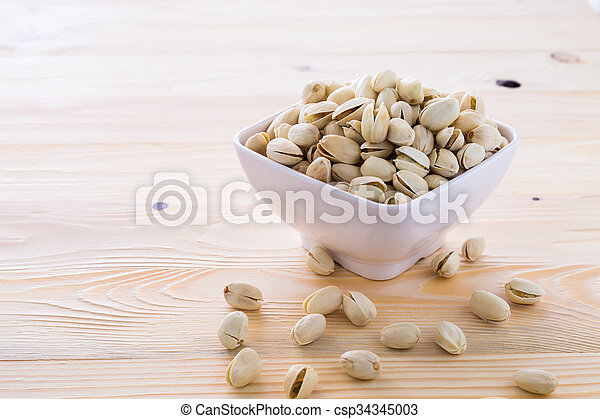 Pistachio nuts in a bowl - csp34345003