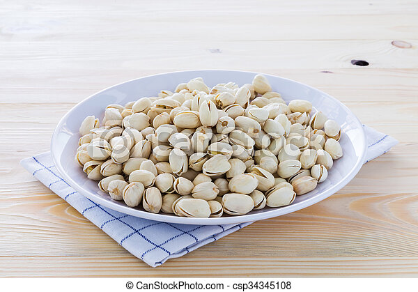 Pistachio nuts in a bowl - csp34345108