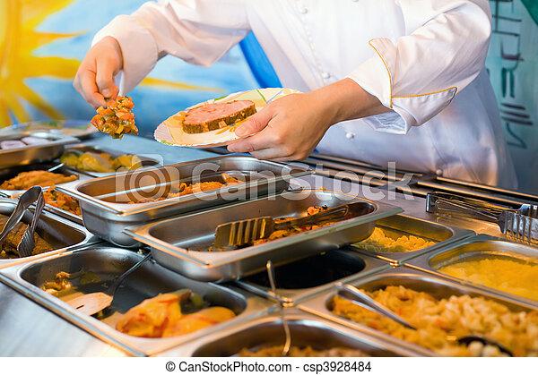 Manos de cocinero colocando platos de verduras en un restaurante público - csp3928484