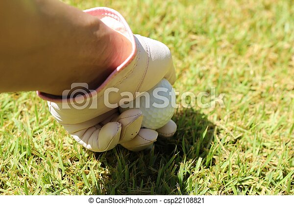 Placing golf ball on a tee - csp22108821
