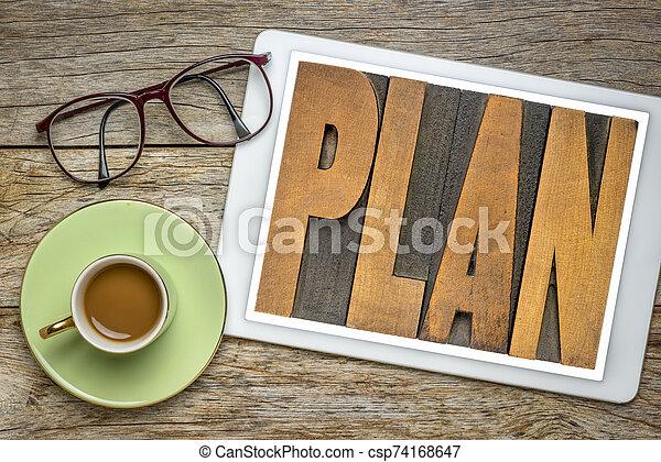 plan word in letterpress wood type on tablet - csp74168647