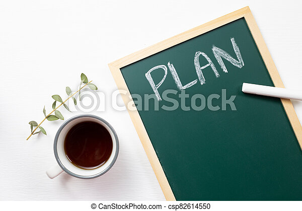 Plan written blackboard with cup of coffee on white background. top view - csp82614550