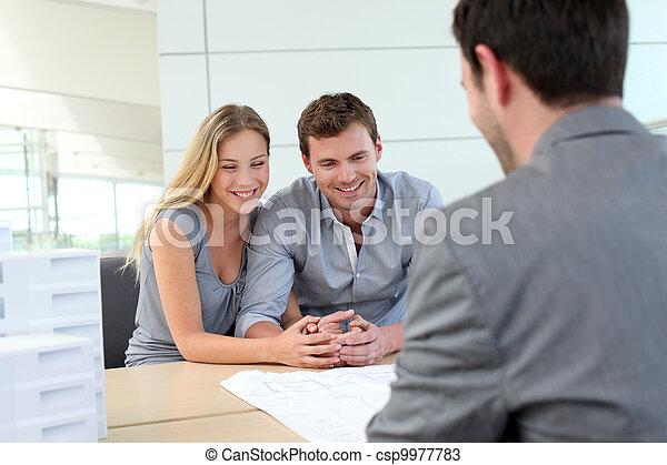 Una pareja en la agencia inmobiliaria hablando con el planificador de construcción - csp9977783