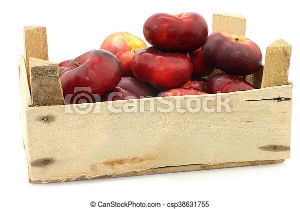 Néctarinas planas frescas en una caja de madera - csp38631755