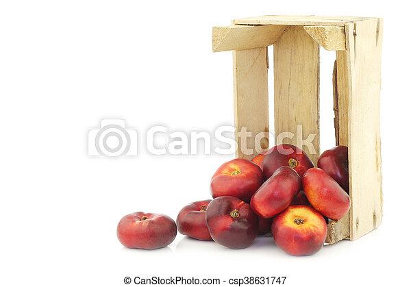 Néctarinas planas frescas en una caja de madera - csp38631747