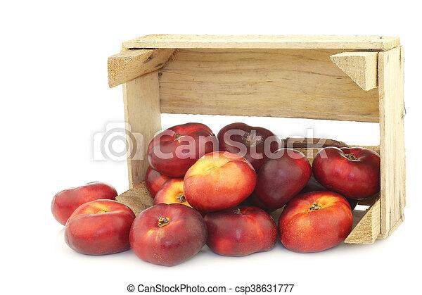 Néctarinas planas frescas en una caja de madera - csp38631777