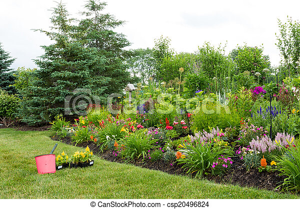 Planting new flowers in a colorful garden - csp20496824